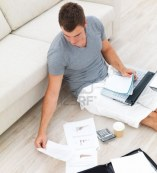 3896390-portrait-of-a-busy-young-man-sitting-on-floor-and-using-a-laptop